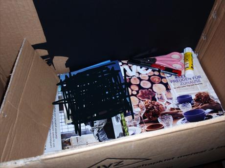 Einen großen Pappkarton, eine Schere, ein Cuttermesser, einen Klebestift, schwarzen Pappkarton, alte Magazine