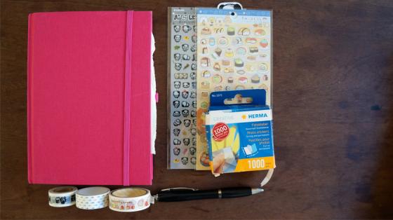 Reisetagebuchmaterialien für eine Reise: Notizbuch, Sticker, Fotoecken, Washitape und Kugelschreiber