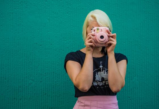 Rosa Polaroidkamera passend zum rosa Faltenrock.