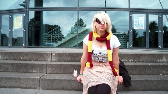 Mädchen mit weißen Haaren, Gryffindor-Schal, weißem T-Shirt und Spitzenrock.