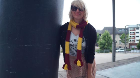 Mädchen mit weißen Haaren, schwarzer Sonnenbrille, gestreiftem Harry Potter-Schal und schwarzer College-Jacke lehnt an Säule.