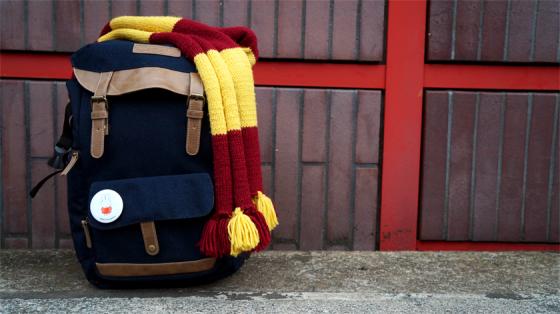 Blauer Rucksack auf dem ein Gryffindor-Schal liegt und an dem ein Miffy-Button befestigt ist.