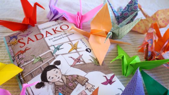 Das Kinderbuch Sadako von Johanna Hohnhold und einige der ikonischen Papierkraniche, die wohl für immer mit Sadakos Schicksal verbunden sein werden.