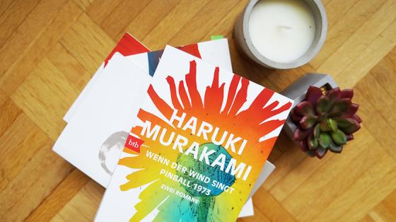 Ein Buchstapel mit Haruki Murakami-Romanen. Oben auf liegt der Doppelband Wenn der Wind singt & Pinball 1973.